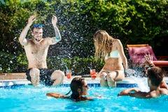 Jeunes amis gais souriant, riant, détente, nageant dans la piscine Photographie stock