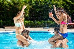 Jeunes amis gais souriant, riant, détente, nageant dans la piscine Image libre de droits