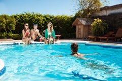 Jeunes amis gais souriant, riant, détente, nageant dans la piscine Image stock