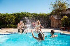 Jeunes amis gais souriant, riant, détente, nageant dans la piscine Photos libres de droits