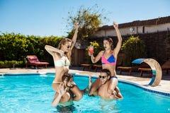 Jeunes amis gais souriant, riant, détente, nageant dans la piscine Images stock