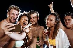 Jeunes amis gais souriant, se réjouissant, faisant le selfie, se reposant à la partie Photographie stock