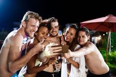 Jeunes amis gais souriant, se réjouissant, faisant le selfie, se reposant à la partie Photos libres de droits