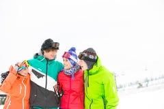 Jeunes amis gais tenant le bras autour dans la neige Photographie stock libre de droits
