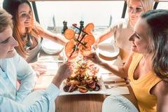 Jeunes amis grillant avec des cocktails avant de manger des fruits de mer à un restaurant Images libres de droits