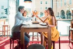 Jeunes amis grillant avec des cocktails avant de manger des fruits de mer à un restaurant Photographie stock libre de droits