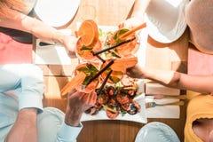 Jeunes amis grillant avec des cocktails avant de manger des fruits de mer Photos libres de droits