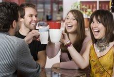 Jeunes amis grillant avec des cuvettes de café Photo stock