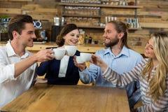 Jeunes amis grillant avec des cuvettes de café Photographie stock