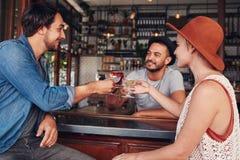 Jeunes amis grillant des boissons au café Photo stock