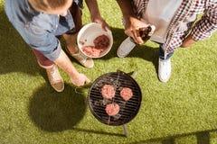 Jeunes amis grillant des hamburgers sur le gril extérieur Photo libre de droits