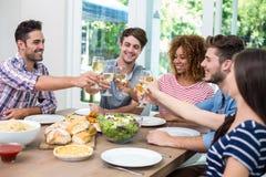 Jeunes amis grillant le vin tout en ayant le repas à la table Photo libre de droits