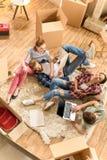Jeunes amis heureux à l'aide de l'ordinateur portable sur le tapis dans la nouvelle maison Image stock