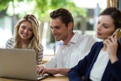 Jeunes amis heureux à l'aide de l'ordinateur portatif Photographie stock