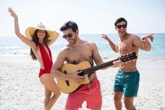 Jeunes amis heureux appréciant à la plage Photo libre de droits