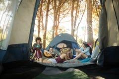 Jeunes amis heureux appréciant ensemble au terrain de camping Image libre de droits