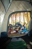 Jeunes amis heureux appréciant ensemble sur le champ au terrain de camping Image stock