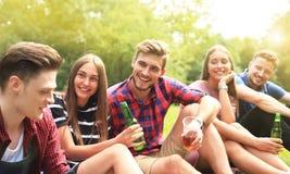 Jeunes amis heureux appréciant le pique-nique et la consommation Photo stock