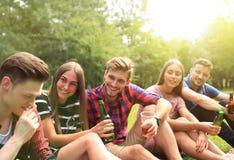 Jeunes amis heureux appréciant le pique-nique et la consommation Image libre de droits