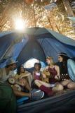 Jeunes amis heureux appréciant tout en se reposant dans la tente Photo stock