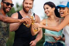 Jeunes amis heureux avec de la bière célébrant et riant dehors Photo libre de droits
