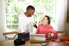 Jeunes amis heureux avec l'appareil-photo d'ordinateur portable et de photo sur la table Photo stock