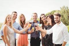 Jeunes amis heureux ayant des boissons Image stock