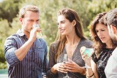 Jeunes amis heureux ayant des boissons Images stock
