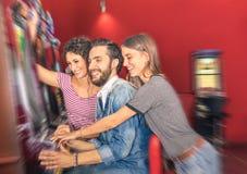 Jeunes amis heureux ayant l'amusement ainsi que la machine à sous Photographie stock