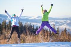 Jeunes amis heureux ayant l'amusement en montagnes d'hiver Image stock