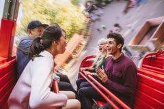 Jeunes amis heureux ayant l'amusement sur le tour de parc d'attractions Images stock
