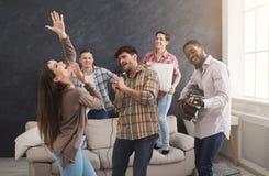 Jeunes amis heureux ayant la partie à la maison Photographie stock libre de droits