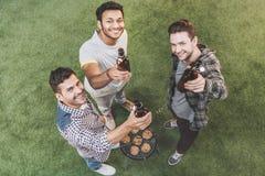 Jeunes amis heureux buvant de la bière et faisant le barbecue Images stock