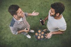Jeunes amis heureux buvant de la bière et parlant tout en faisant le barbecue Photographie stock