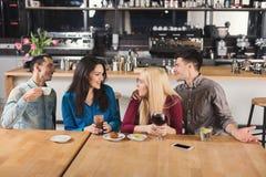 Jeunes amis heureux buvant du café au café Photos stock