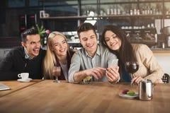 Jeunes amis heureux buvant du café au café Image libre de droits