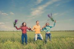 Jeunes amis heureux courant sur le champ de blé vert Photos stock