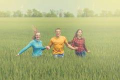 Jeunes amis heureux courant sur le champ de blé vert Photographie stock