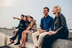 Jeunes amis heureux détendant sur le dessus de toit Images libres de droits