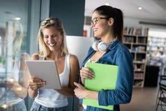 Jeunes amis heureux d'?tudiants ?tudiant avec des livres ? l'universit? photographie stock