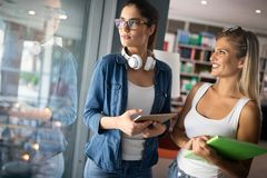 Jeunes amis heureux d'?tudiants ?tudiant avec des livres ? l'universit? photo libre de droits