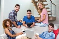 Jeunes amis heureux employant des technologies modernes sur le sofa Photographie stock