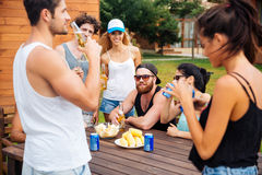 Jeunes amis heureux mangeant et buvant de la bière dehors Images stock