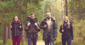 Jeunes amis heureux marchant dans la forêt et appréciant un bon automne Photo stock