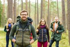 Jeunes amis heureux marchant dans la forêt et appréciant un bon automne Image stock