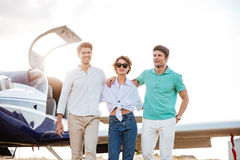 Jeunes amis heureux marchant ensemble sur la piste dans l'aéroport Photos libres de droits