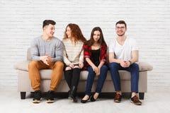 Jeunes amis heureux, personnes occasionnelles s'asseyant sur le divan Photo stock