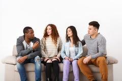 Jeunes amis heureux, personnes occasionnelles s'asseyant sur le divan Photos libres de droits