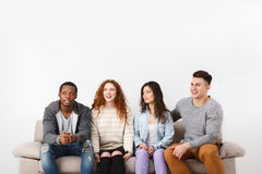 Jeunes amis heureux, personnes occasionnelles s'asseyant sur le divan Photographie stock libre de droits