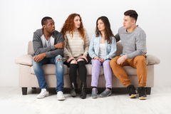 Jeunes amis heureux, personnes occasionnelles s'asseyant sur le divan Photo libre de droits